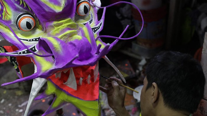 Robert Sicat paints a dragon head as members of a Dragon and Lion dance group seek other ways to earn a living at a creekside slum in Manila's Chinatown, Binondo, Philippines on Feb. 3, 2021. The Dragon and Lion dancers won't be performing this year after the Manila city government banned the dragon dance, street parties, stage shows or any other similar activities during celebrations for Chinese New Year due to COVID-19 restrictions leaving several businesses without income as the country grapples to start vaccination this month. (AP Photo/Aaron Favila)