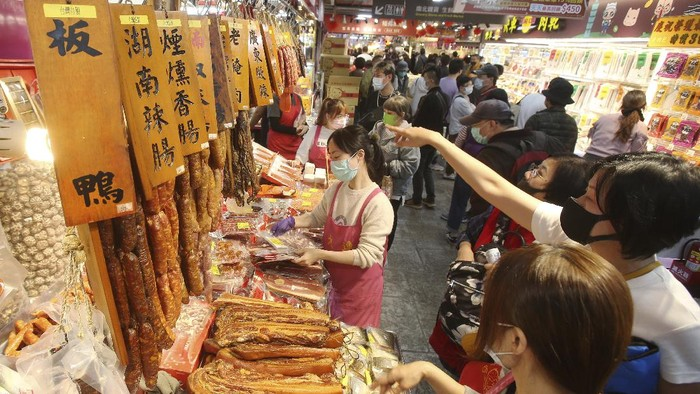 People wear face masks to help curb the spread of the coronavirus as they shop for the upcoming Chinese New Year celebrations at a market in Taipei, Taiwan, Wednesday, Feb 10, 2021. Taiwanese shoppers started hunting for delicacies, dried goods and other bargains at the market ahead of the Lunar New Year celebrations which according to the lunar calendar will take place on Feb. 12. (AP Photo/Chiang Ying-ying)