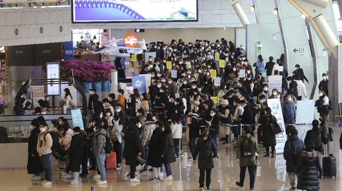 Passengers wearing face masks to help protect against the spread of the coronavirus line up to board planes on the eve of Lunar New Year holiday at the domestic flight terminal of Gimpo airport in Seoul, South Korea, Thursday, Feb. 11, 2021. (AP Photo/Ahn Young-joon)
