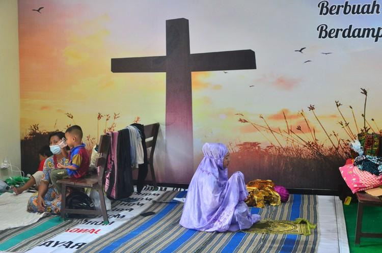 Pengungsi korban banjir berdoa usai melakukan shalat di ruang aula Gereja Kristen Muria Indonesia (GKMI) Tanjung Karang, Kudus, Jawa Tengah, Kamis (11/2/2021). Menurut pengurus gereja setempat, sebagai bentuk toleransi antarumat beragama serta wujud saling membantu kepada sesama, sebanyak 41 warga korban banjir dari berbagai agama dievakuasi ke gereja tersebut sejak 31/1/2021. ANTARA FOTO/Yusuf Nugroho/aww.