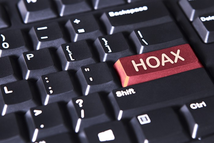 Close up of a computer keyboard with word of hoax on the red button