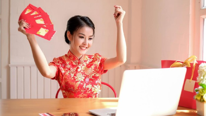Happy chinese new year. asian woman showing angpao in the office smile happily.