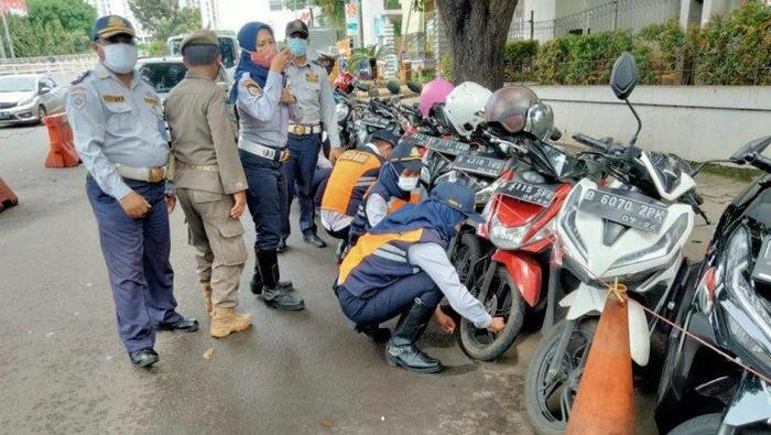 Petugas Suku Dinas Perhubungan Kota Jakarta Selatan melakukan operasi cabut pentil terhada sepeda motor yang diparkir di bahu jalan di Kalibata, Jakarta Selatan, Rabu (10/2/2021)