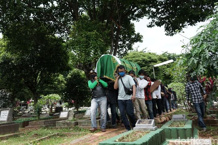 Sejumlah keluarga dan kerabat saat menghadiri pemakaman personil OM PMR, Yuri Anurawan di TPU Gandaria Tengah, Jakarta, Kamis, (11/2/2021).
