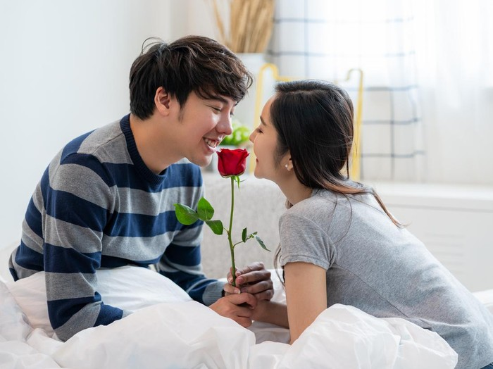 Romantic Asian couple in the bedroom, a man giving a rose to a beautiful woman and both kissing a beautiful rose with love and happiness, Beautiful elegant Asian couple is hugging and smiling in bedroom