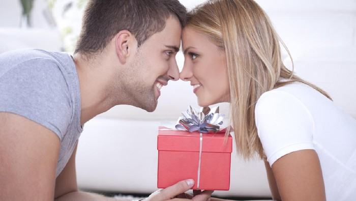 Close up of beautiful young couple and red box gift between them.