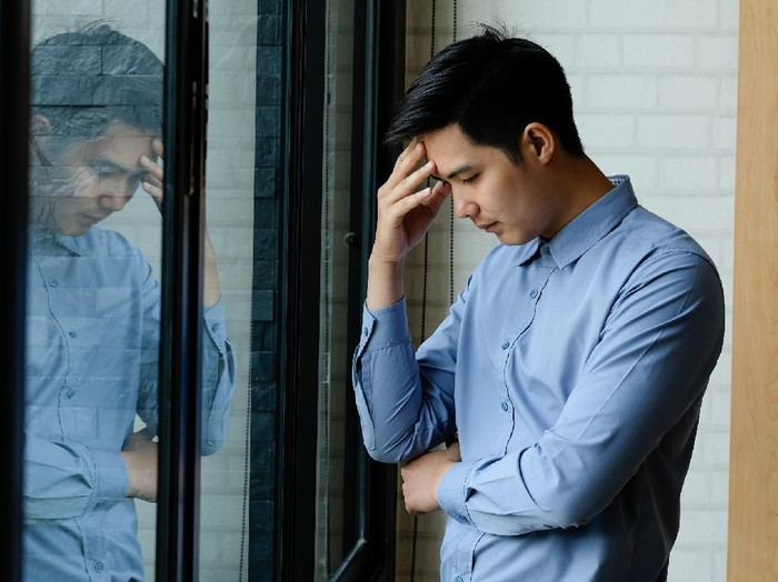 Business man Feeling exhausted massaging headache and stand at his working place in office.