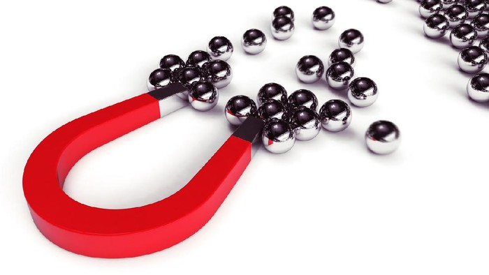 Magnet attracts steel balls from a pile