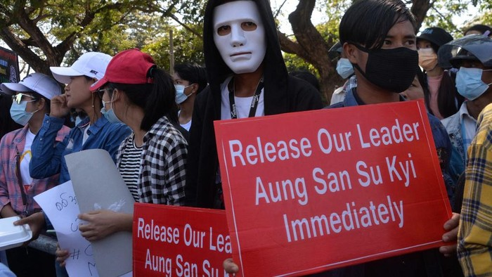 A protester wearing a mask holds up a sign during a demonstration against the military coup in Naypyidaw on February 13, 2021. (Photo by STR / AFP)
