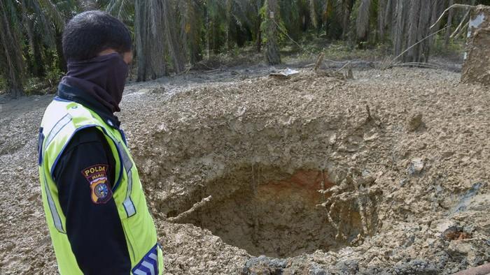 Sejumlah pekerja EMP Bentu mengoperasikan alat berat di tempat semburan gas bercampur lumpur,  di Pondok Pesantren Al-Ihsan, Kota Pekanbaru, Riau, Sabtu (13/2/2021). Tim Dinas ESDM Riau dan perusahaan gas EMP Bentu mulai melakukan proses penutupan lubang berdiameter enam meter dan kedalaman diperkirakan sekitar 119 meter, setelah memastikan semburan gas dan lumpur yang berbahaya sudah berhenti. ANTARA FOTO/FB Anggoro/hp.