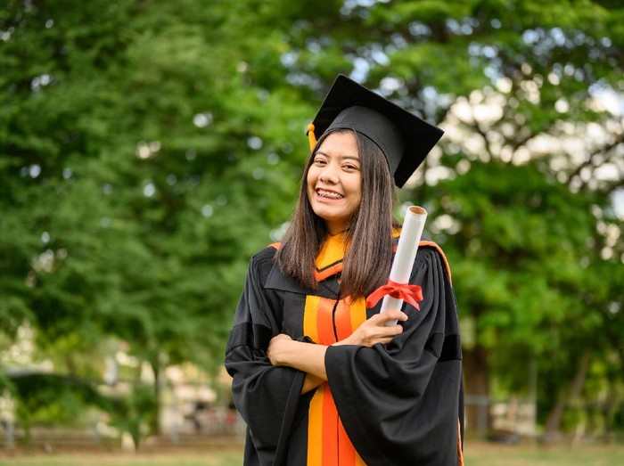 A young female graduate with a scroll in her hands is smiling against the background of university graduates. Graduation.University gesture and people concept.