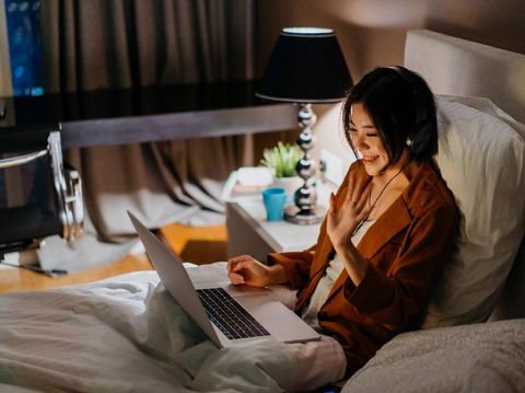 Image of an Asian Chinese woman wearing headphone and video calling in bed with a laptop
