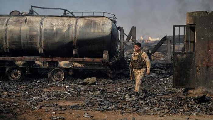 A security forces personnel walks amidst wreckage of gas tankers after a fire accident at Islam Qala on the outskirts of Herat, in the border between Afghanistan and Iran on February 14, 2021. (Photo by HOSHANG HASHIMI / AFP)