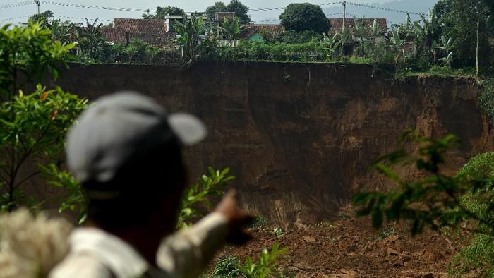 Hujan deras yang mengguyur kawasan Garut, Jawa Barat, menyebabkan tebing longsor. Akibatnya, ratusan warga mengungsi ke tempat aman guna cegah longsor susulan.