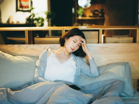 Young Asian woman feeling sick and suffering from a headache, lying on the bed and taking a rest at home