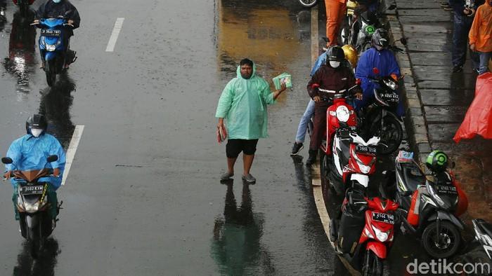 Hujan deras yang mengguyur wilayah Jakarta dan sekitarnya menjadi berkah bagi penjual jas hujan. Dagangannya laris dibeli pengendara sepeda motor.