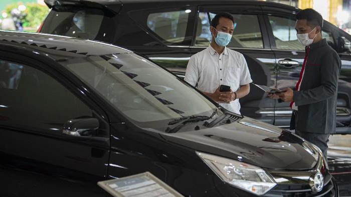 Karyawan menjelaskan salah satu produk mobil kepada calon pembeli di salah satu dealer di Jakarta, Senin (15/2/2021). Pemerintah memberikan keringanan pajak penjualan atas barang mewah (PPnBM) mobil baru ketegori 4x2 atau sedan dengan mesin sampai dengan 1.500 cc mulai Maret 2021 dengan tiga tahap untuk meningkatkan pertumbuhan industri otomotif dengan local purchase kendaraan bermotor di atas 70 persen. ANTARA FOTO/Aditya Pradana Putra/hp.