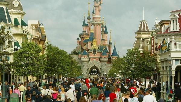 Kerumunan turis berjalan menuju kastil Sleeping Beauty di Disneyland Paris. Disneyland menjadi salah satu tempat yang paling banyak dikunjungi di seluruh dunia. Getty Images/Pascal Le Segretain
