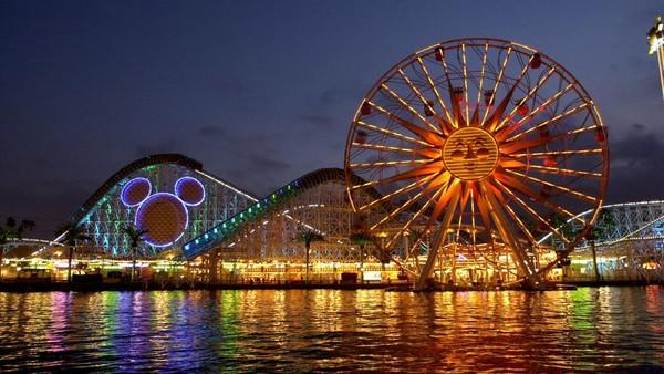 Wahana roller coaster dan kincir angin tampak di Disneyland California, Amerika Serikat. Disneyland pertama dibuka di California, Amerika Serikat, pada 17 Juli 1955. Kini, 66 tahun berselang, taman hiburan tematis ini berkembang di beberapa negara.