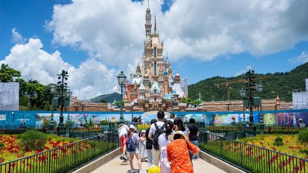 Pengunjung mengambil foto Castle of Magical Dreams di Walt Disney Co.s Disneyland Resort Hong Kong. Disney merancang Disneyland dan taman lanjutannya Disney California sebagai taman bagi keluarga tempat orangtua dan anak-anak. Getty Images/Billy H.C. Kwok