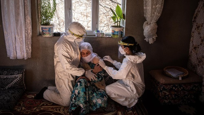 VAN, TURKEY - FEBRUARY 11: Nurse, Bilge Koc and nurse, Gokalp Balli of the Gevas Public Health Center vaccination team, prepare to vaccinate 81 year old Selim Saypak with the Chinese Sinovac Coronavac vaccine during a house call in the village of Ikizler on February 11, 2021 in Van, Turkey.  Since shipments of the Chinese Sinovac Coronavac vaccine arrived in Turkey on December 30, 2020, medical teams across the country have been working house to house to administer the COVID-19 vaccine to elderly and vulnerable citizens. For the members of the Van City, Gevas Province Public Health Centre vaccination teams, who specialise in remote locations, often high in the mountains or villages that have become inaccessible by car, due to heavy snowfall and road closures, house calls pose many unique challenges. The teams are often forced to hand carry the vaccine for kilometres through deep snow and mud to gain access to the village and administer the vaccine. Since the start of the vaccine campaign in Turkey the two specialist mobile teams have vaccinated more than 130 citizens in rural villages, some as old as 106. Turkeys official drug and medical equipment body approved the Chinese Sinovac Coronavac vaccine for emergency use against the novel coronavirus on the 13th of January 2020. According to data from Turkey's Health Ministry the country has vaccinated more than 3.6 million people. The death toll from the coronavirus in Turkey has reached more than 27,000 and the number of infections has topped 2.5 million since mid-March 2020. Globally more than 107 million people have been infected by the virus. (Photo by Chris McGrath/Getty Images)