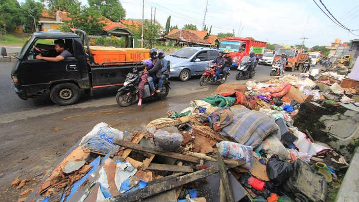 Pengendara melintas di sekitar sampah yang menumpuk di tepi jalur Pantura Losarang, Indramayu, Jawa Barat, Senin (15/2/2021). Sampah yang terbawa banjir beberapa hari lalu dibiarkan menumpuk di tepi jalur pantura dan menimbulkan aroma yang tidak sedap. ANTARA FOTO/Dedhez Anggara/hp.