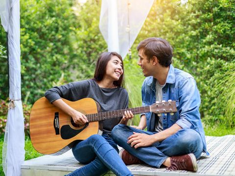 Young Asian loving couple playing guitar in the park, outdoors
