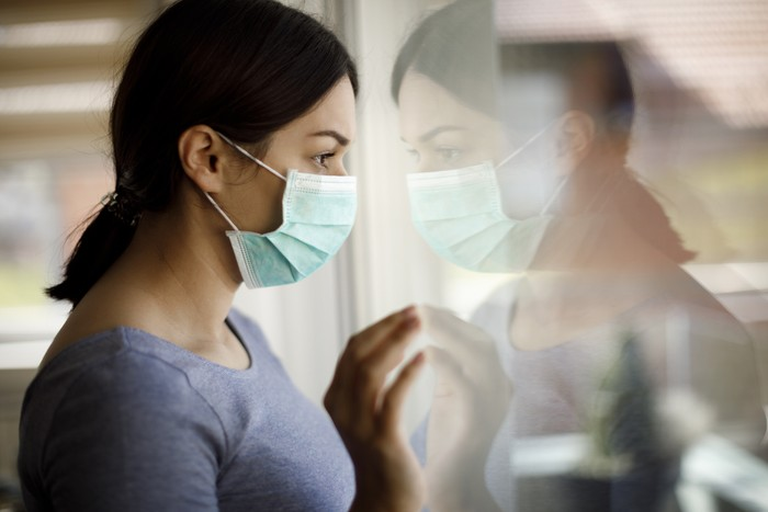 Portrait of sad young woman with face protective mask looking through the window at home