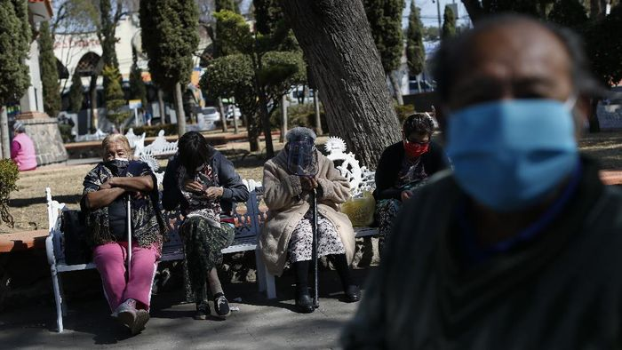 A wheelchair-bound elderly person who got a shot of the AstraZeneca vaccine against COVID-19 is pushed to an observation area, at a vaccination center set up in the Magdalena Contreras area of Mexico City, Monday, Feb. 15, 2021, as Mexico starts vaccinating people over age 60 against the new coronavirus. (AP Photo/Marco Ugarte)