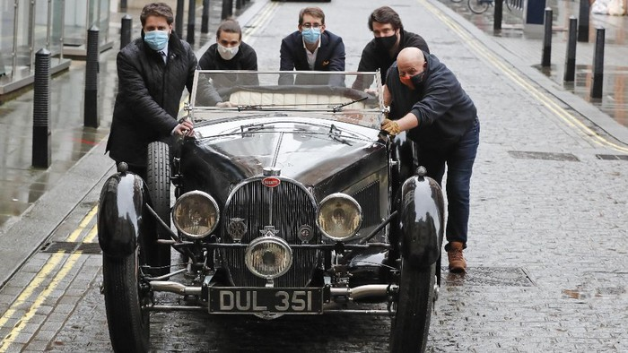 A 1937 Bugatti Type 57S, one of the world's most valuable and desirable pre-war motor cars, is polished by staff at the Bonhams auction house in London, Tuesday, Feb. 16, 2021. Bonhams Legend of the Road Sale is featuring a 1937 Bugatti Type 57S, with an estimate £5,000,000 - 7,000,000. The Bugatti has been hidden for the past 50 years and is one of 42 examples of the 57S variants that were produced. (AP Photo/Frank Augstein)