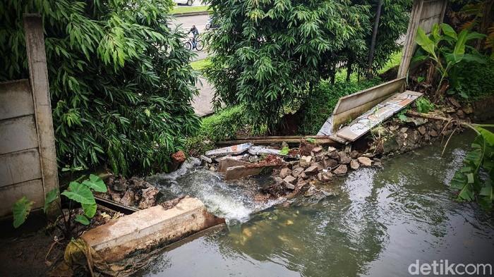 Warga melintas di tali air atau saluran air yang jebol sepanjang 3 meter di RT 03 RW 04, Parigi, Pondok Aren, Tangerang Selatan, Rabu (17/2/2021).