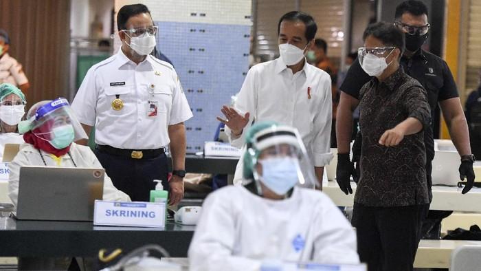 Presiden Joko Widodo (tengah) didampingi Menteri Kesehatan Budi Gunadi Sadikin (kanan) dan Gubernur DKI Jakarta Anies Baswedan meninjau vaksinasi COVID-19 massal bagi pedagang di Pasar Tanah Abang Blok A, Jakarta, Rabu (17/2/2021). Vaksinasi COVID-19 tahap kedua yang diberikan untuk pekerja publik dan lansia itu dimulai dari pedagang Pasar Tanah Abang. ANTARA FOTO/Hafidz Mubarak A/wsj.