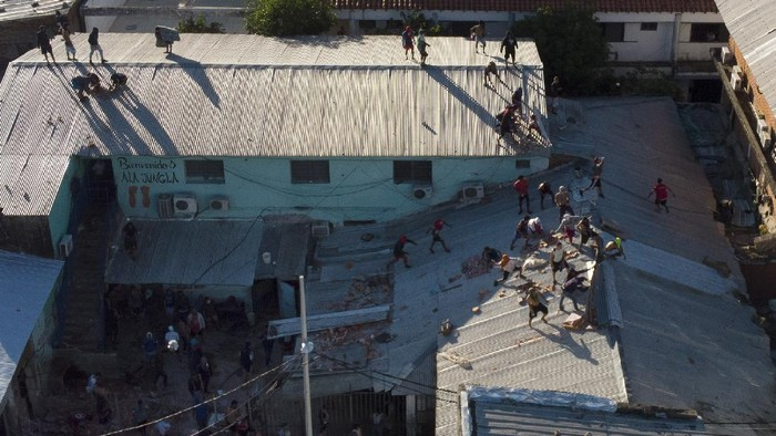Inmates throw bricks at the police from the roof of Tacumbu prison during a riot and after they took control of the place in Asuncion, Paraguay, Tuesday, Feb. 16, 2021. (AP Photo/Jorge Saenz)