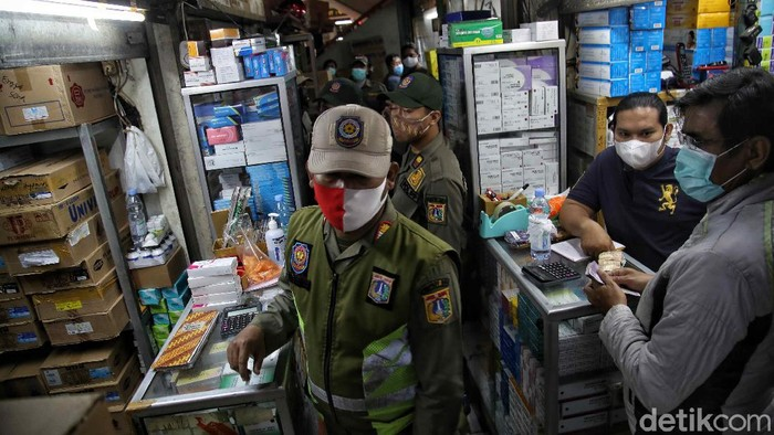 Petugas gabungan melakukan sidak masker di kawasan Pasar Pramuka, Jakarta Timur. Sidak dilakukan dalam rangka PPKM Mikro.