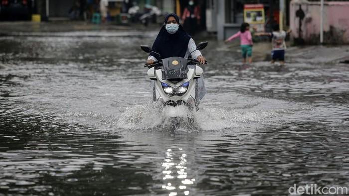 Banjir merendam Perumahan Taman Duta, Depok, Jawa Barat, Jumat (19/2/2021). Para pengendara pun nekat menerobos banjir di perumahan tersebut.