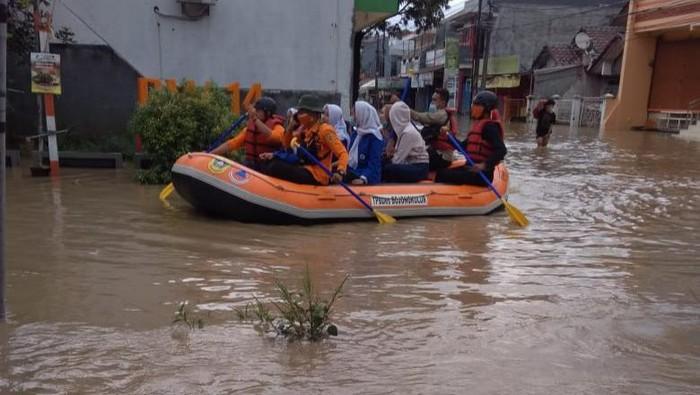 Petugas mengevakuasi korban terdampak banjir di Perum Vila Nusa Indah Gunungputri Bogor, Jumat (19/2/2021).