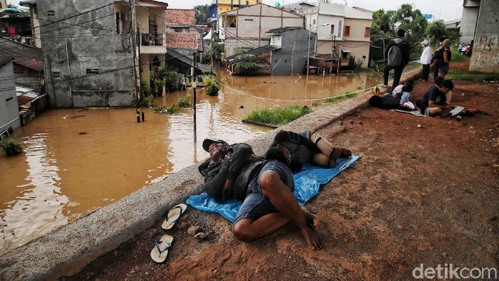 Banjir merendam kawasan Cipinang Melayu, Makasar, Jakarta Timur, Jumat (19/2/2021). Sebagian warga yang terdampak mulai mengungsi di kolong tol Becakayu.