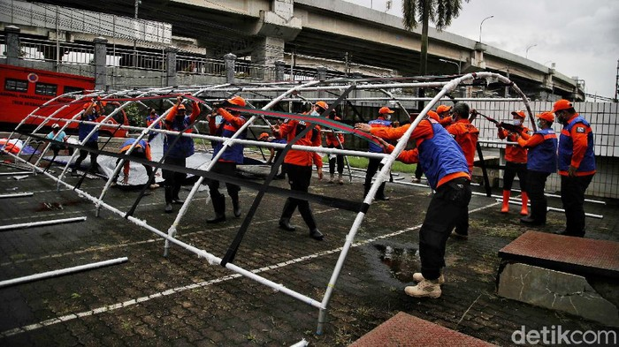 Petugas BPBD (Badan Penangulangan Bencana Daerah) DKI Jakarta membangun posko banjir di kawasan Universitas Borobudur, Kalimalang, Cipinang Melayu, Jakarta Timur, Jumat (19/2). Posko tersebut nantinya digunakan untuk petugas membantu evakuasi korban banjir di kawasan Cipinang Melayu serta memastikan logistik aman untuk korban banjir