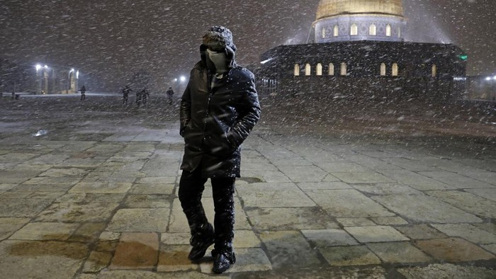 A Palestinian man walks as snow falls at the Dome of the Rock Mosque in Jerusalems al-Aqsa mosque compound, on February 17, 2021. (Photo by Ahmad GHARABLI / AFP)
