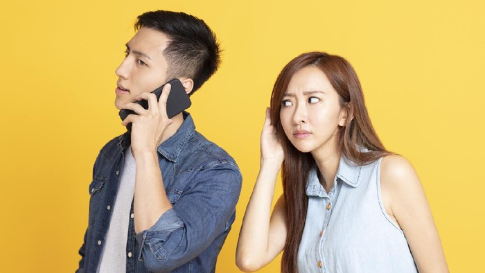 Man and woman listening on the mobile phone