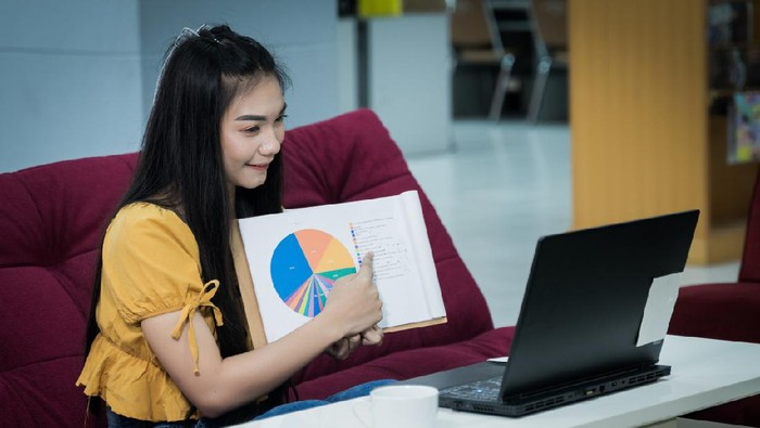 A young Asian female university student presents chart on her project study online via laptop at home during COVID-19 pandemic to practice social distancing. Stock photo.