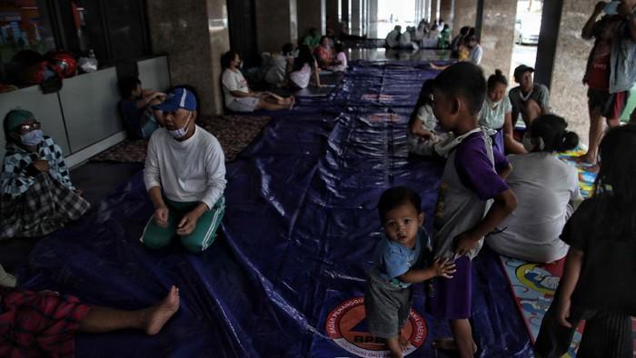Sejumlah warga korban banjir mengungsi di sudut ruangan Universitas Borobudur, Kalimalang, Jakarta timur, Jumat (19/2).