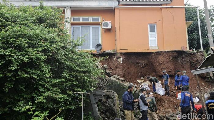 Petugas tengah melakukan pembersihan sisa-sisa longsor di kawasan Griya Merdeka Timur, Depok, Jawa Barat, Jumat (19/2/2021).