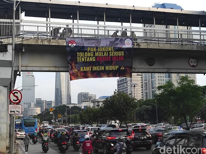 Mahasiswa Trisakti pasang spanduk soal krisis iklim di JPO Semanggi dan JPO Slipi. (Azhar Bagas Ramadhan/detikcom)