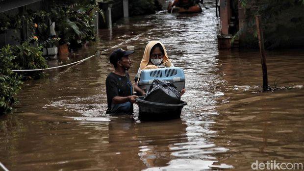 Sejumlah warga menerobos banjir di kawasan Kampung RW04 Cipinang Melayu, Jakarta Timur, Jumat (19/2). Saat ini banjir setinggi 1 meter lebih masih menggenangi kawasan banjir tersebut dan diprediksi jika hujan lagi maka akan lama surutnya