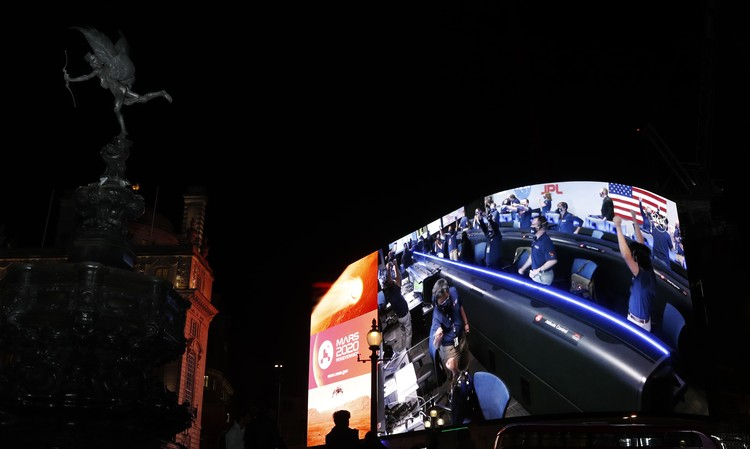 Images from Nasa are streamed live showing the landing of NASAs Perseverance on Mars, shown on Piccadilly Lights in central London, Thursday Feb. 18, 2021.  The Mars rover landing mission begins its search for traces of life after the successful landing, to explore and collect samples for future return to Earth. Eros statue top left. (AP Photo/Alastair Grant)
