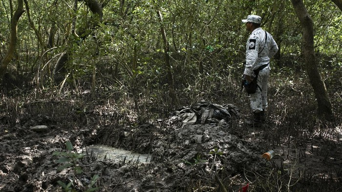 Investigators from the National Search Commission take a boat in Puquita a tropical mangrove island, near Alvarado in the Gulf coast state of Veracruz, Mexico, where a clandestine grave site has been found, Thursday, Feb. 18, 2021. Investigators found three pits with human remains and plastic bags inside. The number of bodies there has not yet been determined. (AP Photo/Felix Marquez)