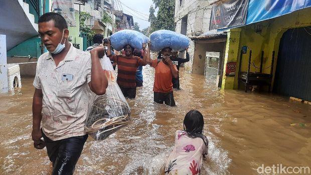 Sejumlah warga mengamankan barang-barang pribadi dari lokasi banjir di RT 03 RW 04 Cipinang Melayu pukul 13.00 WIB (Rahmat Fathan/detikcom).