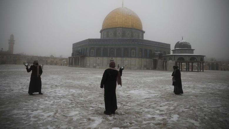 Wanita bermain di Kubah Batu di komplek Masjid Al Aqsa yang diselumuti salju, Kamis  Feb. 18, 2021. (AP Photo/Mahmoud Illean)