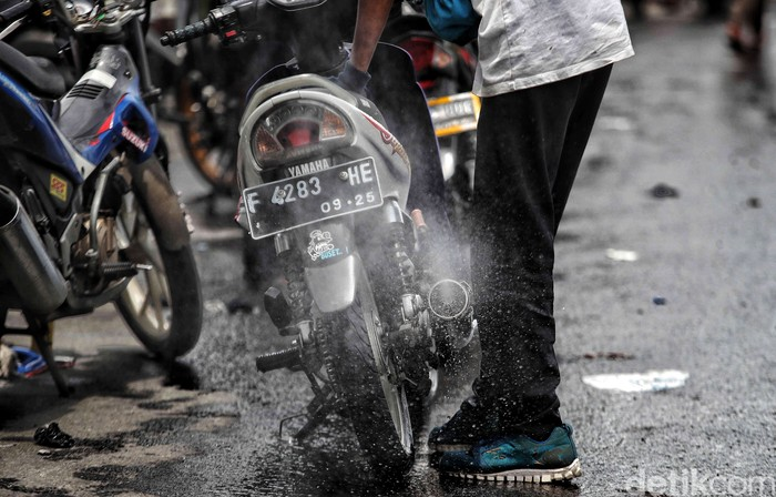Sejumlah tukang bengkel keliling memperbaiki motor warga yang mati akibat menerobos banjir di kawasan Jalan Kapuk Raya, Penjaringan, Jakarta Utara, Sabtu (20/2). Jasa servis motor tersebut berkisar pada harga Rp. 25.000-Rp.100.000 tergantung tingkat kerusakan dan jasa bongkar mesin. Biasanya kebanyakan motor banjir rusak di busi dan karbu
